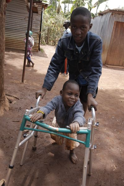 Hilliary helping Moses with the walker before he started walking independently.